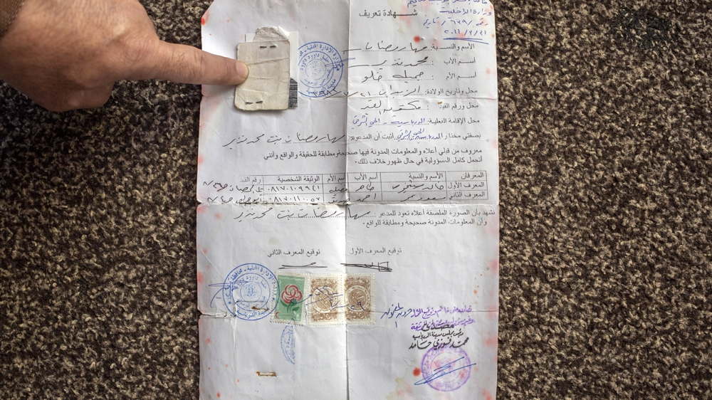 Abu Mohammed points at his wife's Syrian identification papers, which is often given to those without citizenship