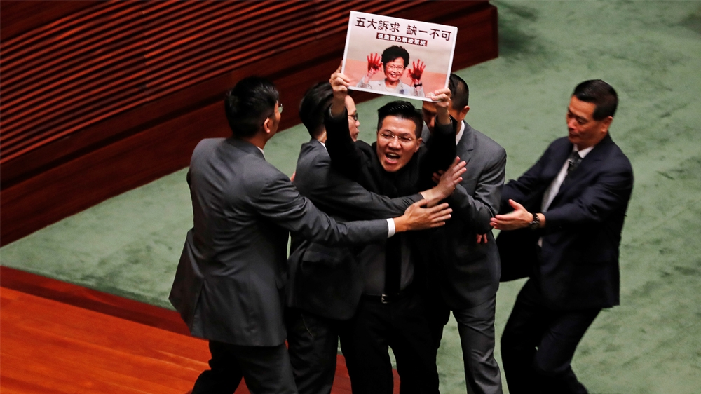 Pro-democracy lawmaker Wu Chi-wai holding a placard is escorted by security from the Legislative Council, as Hong Kong's Chief Executive Carrie Lam takes questions from lawmakers