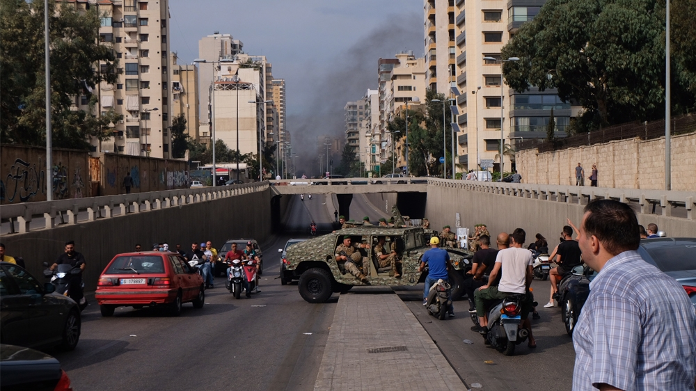 A convoy of Army Humvees turns around after being confronted with demonstrators on a roadblock in central Beirut. [Timour Azhari/Al Jazeera]