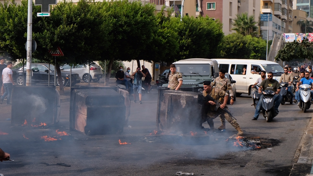 A soldier tries to clear a way through smoldering garbage cans and burning tires on the outskirts of downtown Beirut. [Timour Azhari/Al Jazeera]