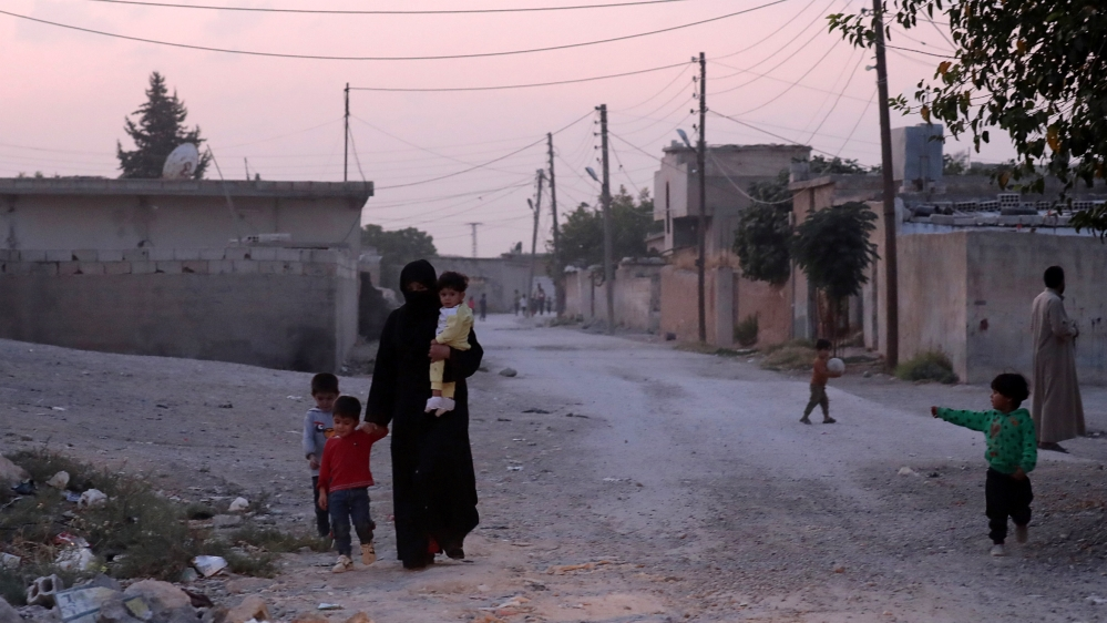 A woman holds a child as she walks along a street in the border town of Tal Abyad