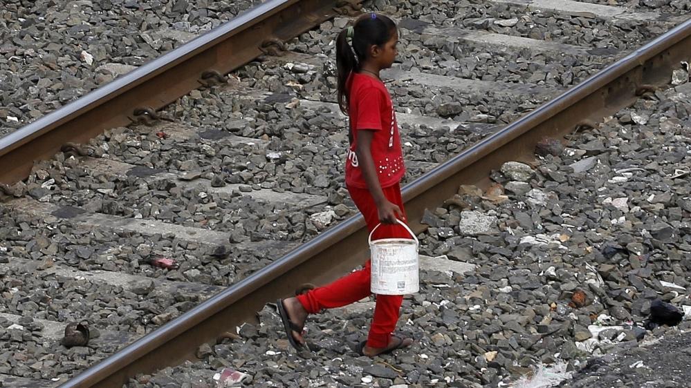 In this June 30, 2015 file photo, an Indian girl holds a can filled with water and walks past railway tracks to defecate in the open in Mumbai, India. The numbers in the government's ambitious Swachh