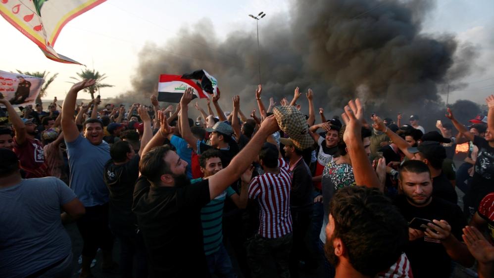 Los manifestantes gritan consignas mientras bloquean el camino con neumáticos en llamas durante una protesta por el desempleo, la corrupción y los servicios públicos deficientes, en Bagdad