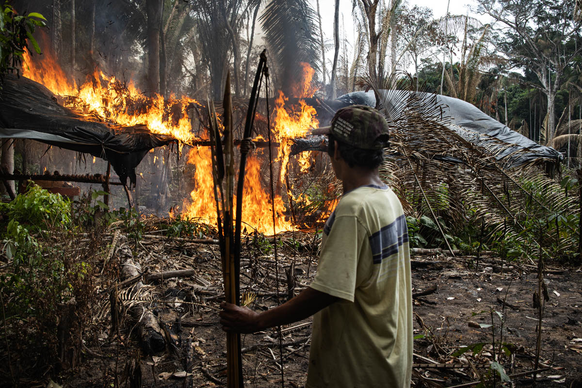 Purua, 45, of the Uru-Eu-Wao-Wao tribe, set fire to a land grabbers' hut inside his tribe's reserve. In September 2019, a group of land-grabbers that deforested the territory was intercepted by the Funai (government agency for the protection of indigenous people) and arrested by police inside the Uru-Eu-Wao-Wao reserve. A group from Purua's tribe returned to the scene to set fire to the illegal hut so they can not return. [Fabio Bucciarelli/Al Jazeera]