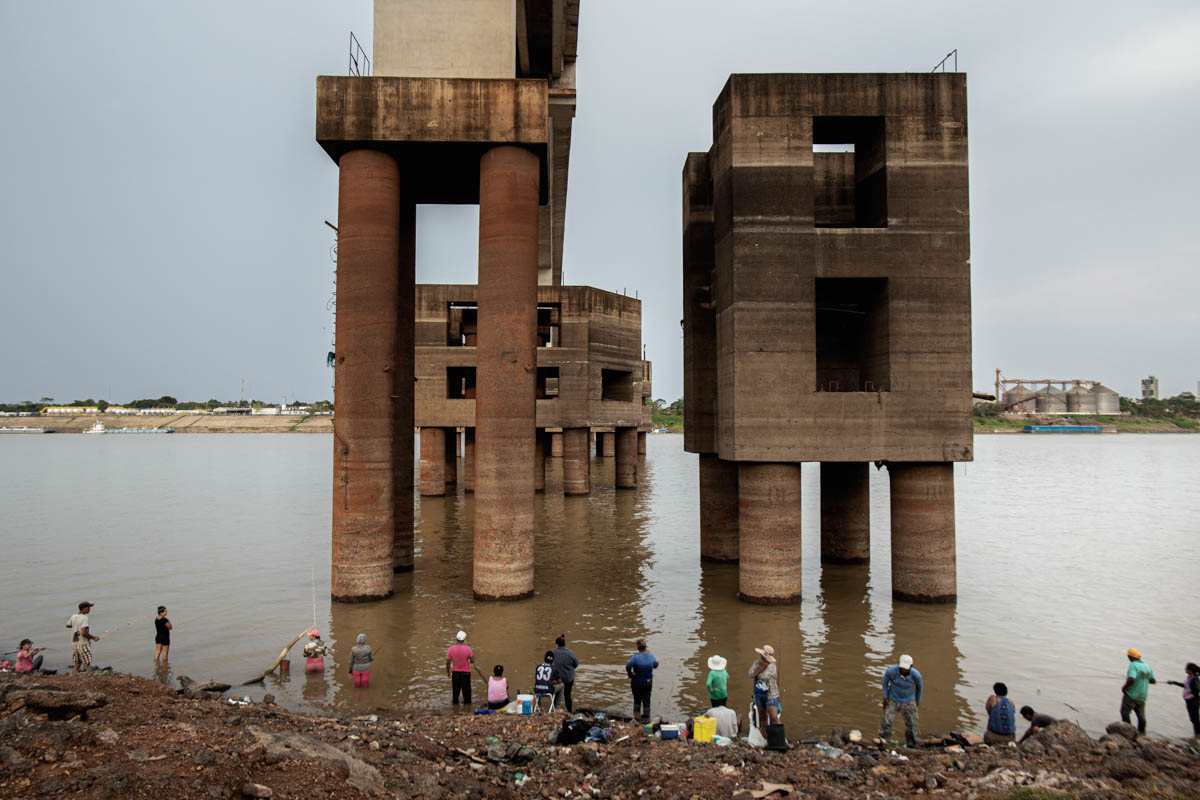 Fishermen under a bridge that crosses the Madeira River in Porto Velho. In the background, silos are used to store soya, which is among the world's most cultivated food products. [Fabio Bucciarelli/Al Jazeera]