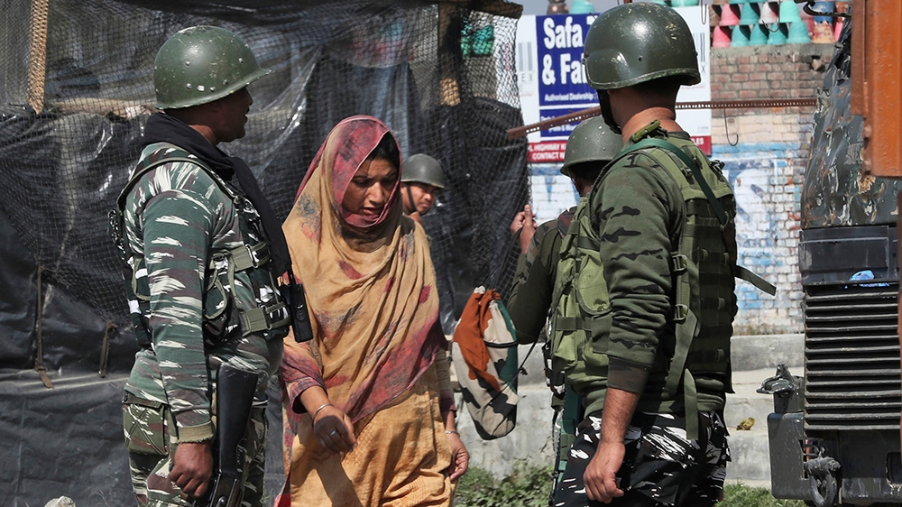 Indian paramilitary soldier guard as a Kashmiri villager woman walks near the site of gun-battle in south of Srinagar, Indian controlled Kashmir, Wednesday, Oct. 16, 2019. (AP Photo/Mukhtar Khan)