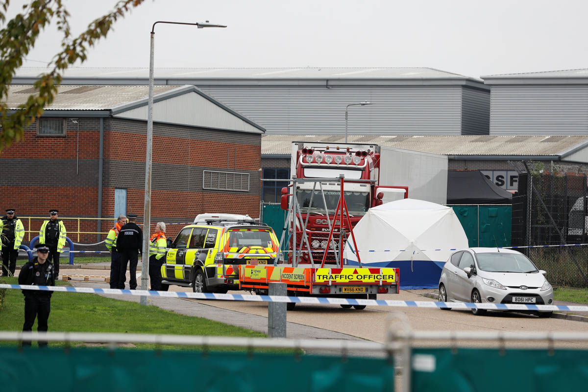 Police at the scene where bodies were discovered in a truck container, in Grays, Essex. [Peter Nicholls/Reuters]