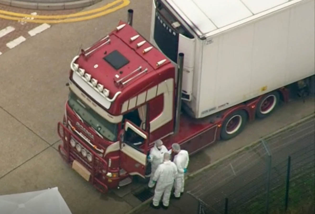 An aerial view as police forensic officers attend the scene after a truck was found to contain a large number of human bodies, in Thurrock, South England. [AP Photo]