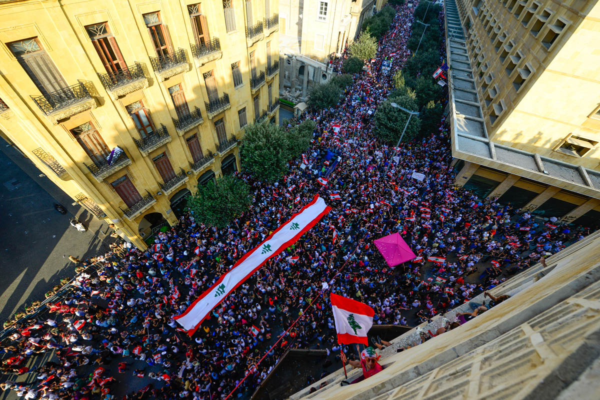 A giant Lebanese flag is carried by the crowd, stretching from the Grand Serail government buildings to the Grand Mosque in Martyrs' Square. More than one million people were peacefully protesting on Beirut's streets by the third day. [Alexander Lerche/Al Jazeera]