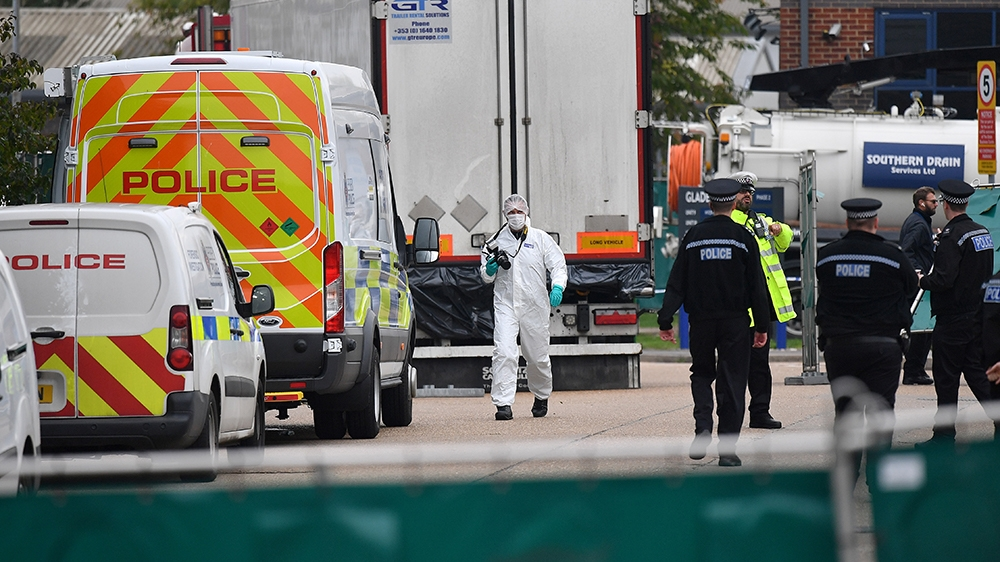 British Police officers in forsensic suits work near a lorry, found to be containing 39 dead bodies, as they work inside a police cordon at Waterglade Industrial Park in Grays, east of London, on Octo
