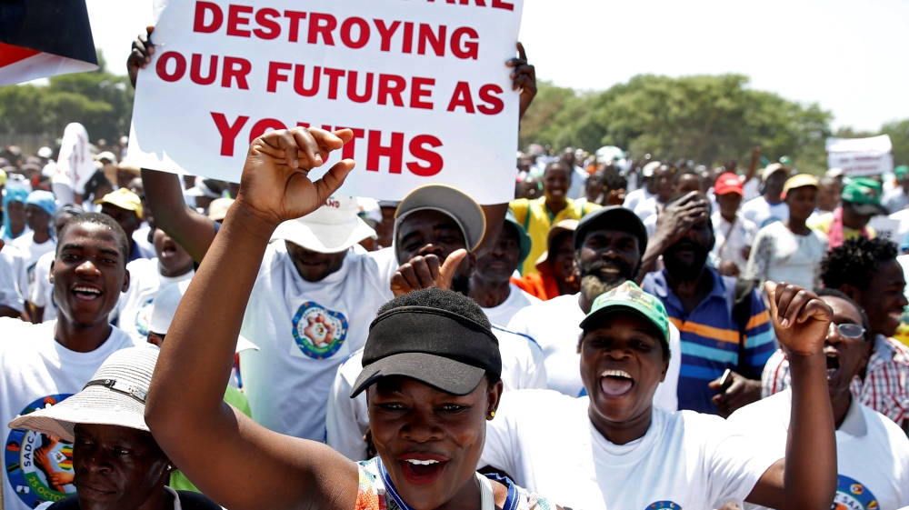 Government supporters chant slogans as they march against Western sanctions at a rally in Harare