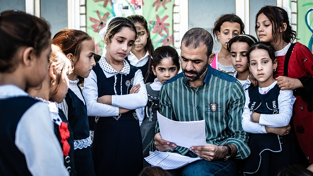 A teacher counting students in the schoolyard due to a lack of school building - back to school day 2019-2020 in Aljaleel school, Mosul [Tom Peyre-Costa/NRC]