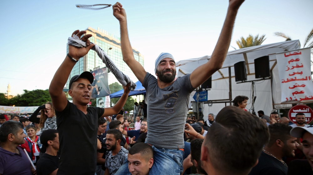 Protestors celebrate after the Prime Minister Saad al-Hariri announced his resignation, in Sidon
