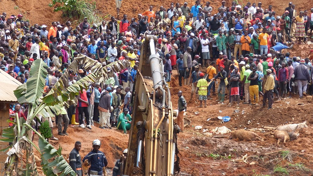 Rescue workers search through the rubble following a landslide in Bafoussam Cameroon, Tuesday, Oct. 29, 2019.  Cameroon on Monday deployed rescue workers and its military to search the wreckage of hou
