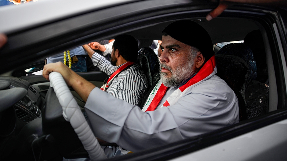 Iraqi Shiite cleric Moqtada al-Sadr (R) drives a car as he joins anti-government demonstrators gathering in the central holy city of Najaf on October 29, 2019. - Sadr, who has backed the protests, was