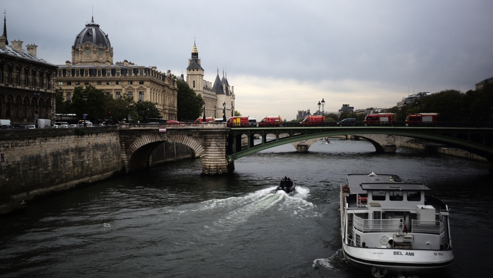 Rescue vehicles park on the bridge leading to the Paris police headquarters, left, Thursday, Oct.3, 2019