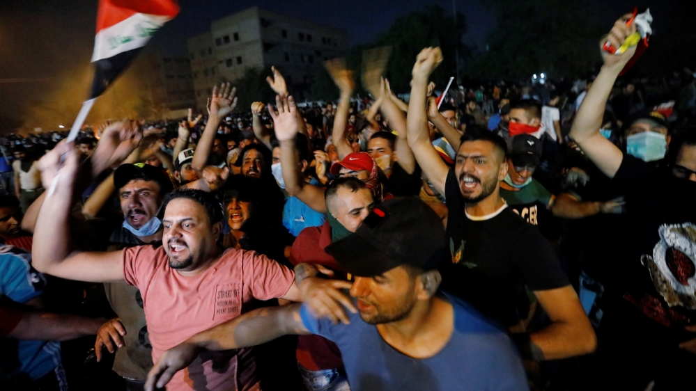 Demonstrators gather at a protest during a curfew, two days after the nationwide anti-government protests turned violent, in Baghdad
