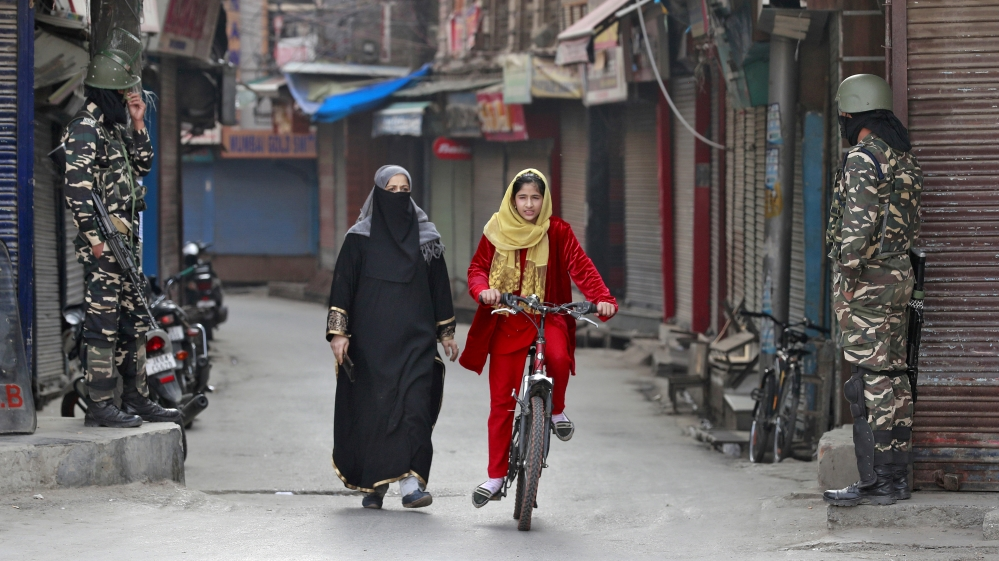 A Kashmir girl rides her bike past Indian security force personnel standing guard in front closed shops in a street in Srinagar