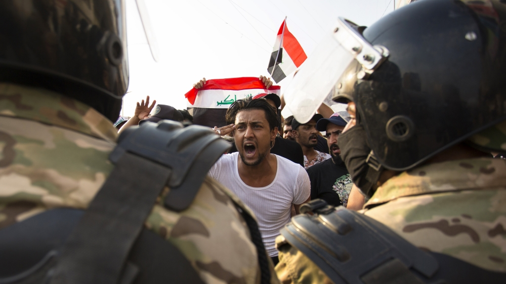 An Iraqi protestor gestures in front of security forces