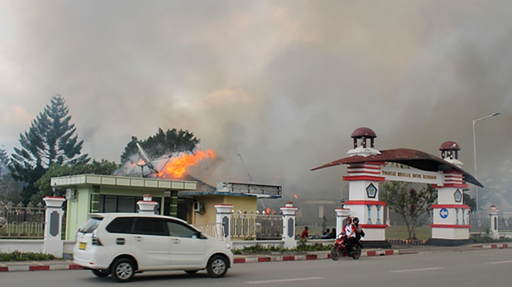 A car passes governor office building of Jayawijaya burned during a protest in Wamena, Papua