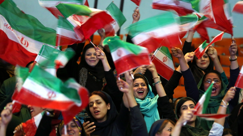 Iranian women wave Iranian flags during a ceremony of farewell for their national soccer team ahead of the 2014 World Cup in Brazil, at the hall of Azadi (freedom) sports compound in Tehran, Iran, Mon