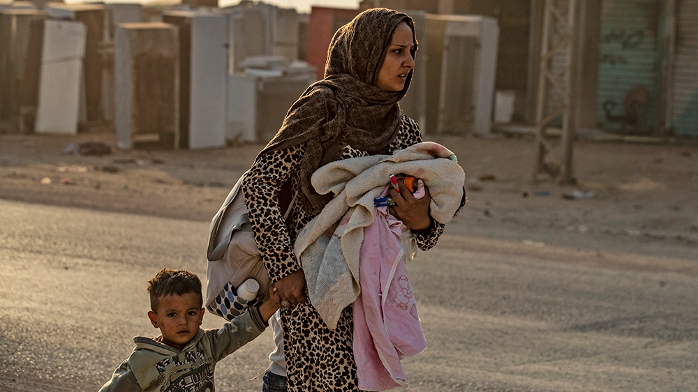 A woman flees with her children amid Turkish bombardment on Syria