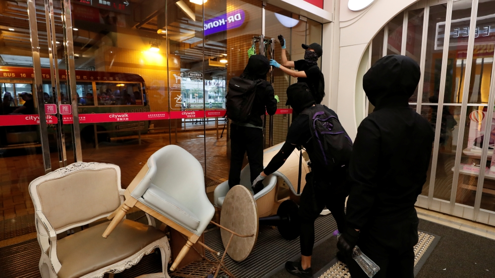 Hong Kong police shoot protester as activists block streets