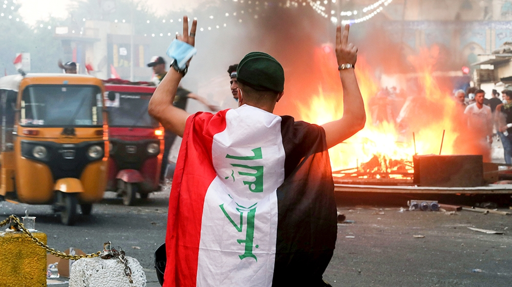 Anti-government protesters set fire and close streets during ongoing protests in Baghdad, Iraq, in central Baghdad, Iraq, Saturday, Nov. 9, 2019. (AP Photo/Hadi Mizban)