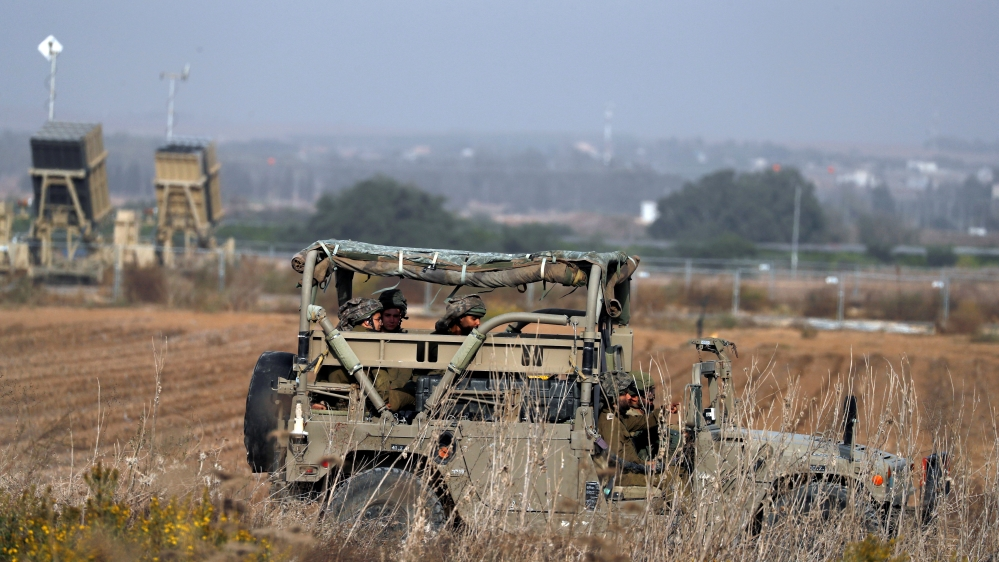 Israeli soldiers ride a military jeep in an area near the Gaza border, in southern Israel