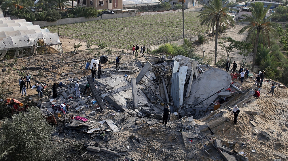Palestinians gather around the remains of a house destroyed in an Israeli air strike in the southern Gaza Strip November 13, 2019. REUTERS/Ibraheem Abu Mustafa