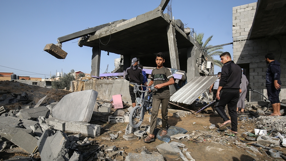 Palestinian youths look for salvageable items amid the rubble of a house destroyed in an Israeli air strike in Khan Yunis in the southern Gaza Strip November 13, 2019. - Two Palestinians were killed i