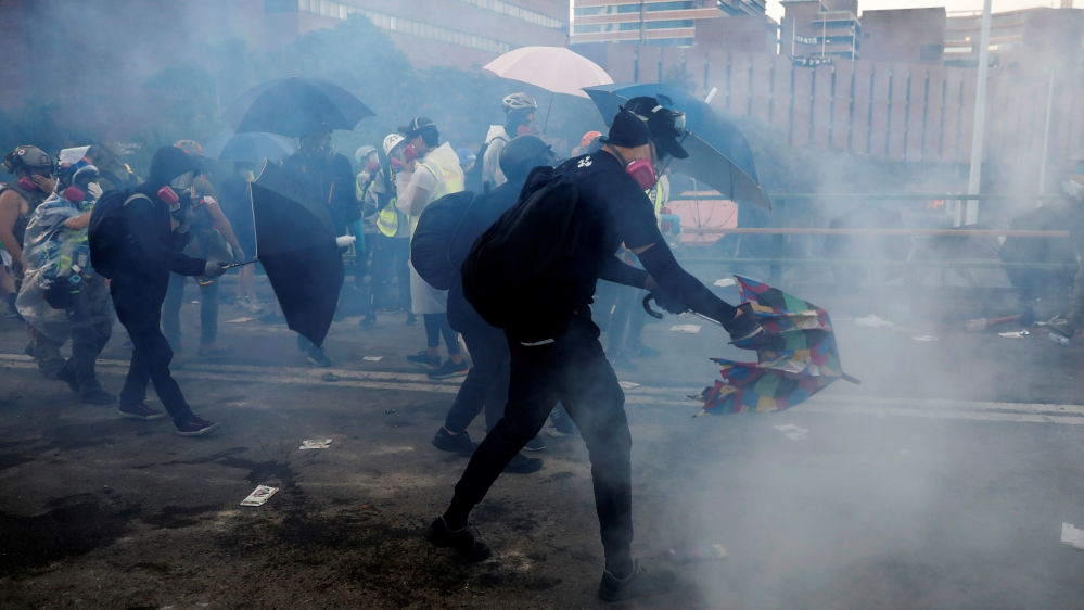 Protesters take cover during clashes with police outside Hong Kong Polytechnic University