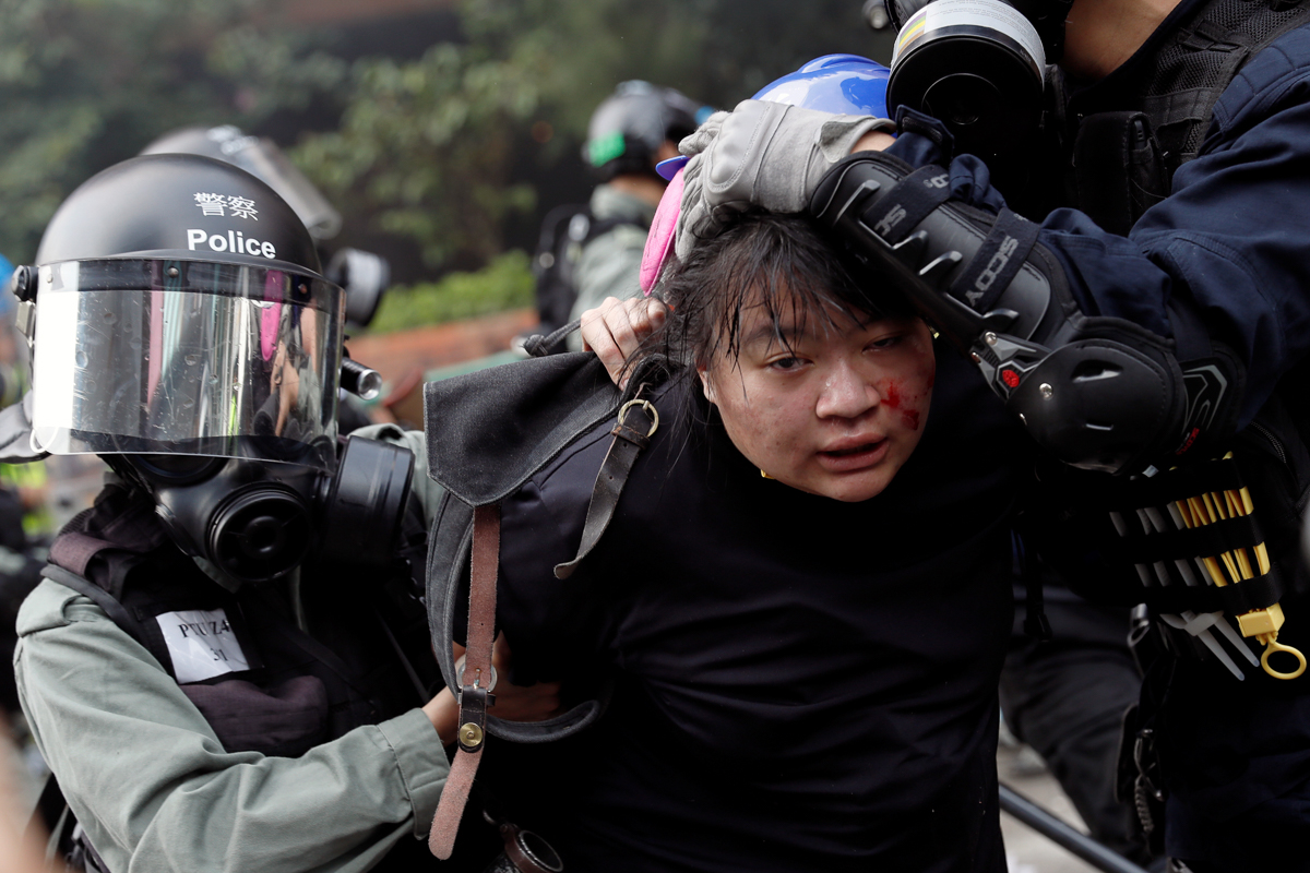 A protester attempting to leave the campus is detained by police. [Tyrone Siu/Reuters]