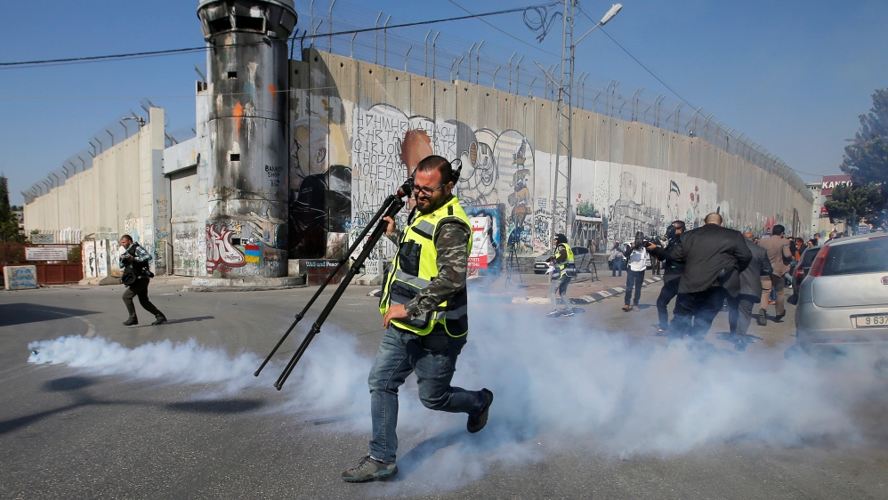 Palestinian journalist runs away from tear gas fired by Israeli forces during a protest to show solidarity with his colleague Muath Amarna, who was shot in his eye, in Bethlehem