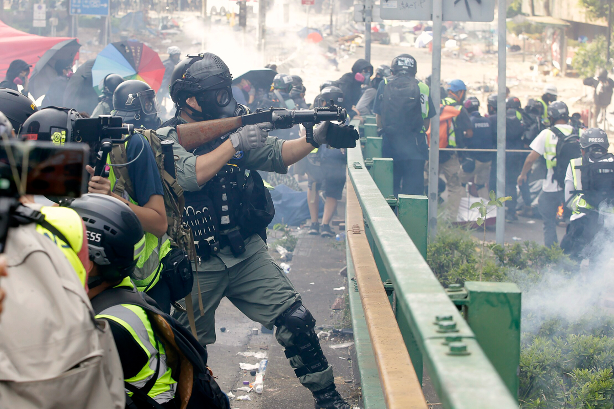 Riot squads cordoned off the campus after they attempted to storm the site. [Achmad Ibrahim/AP Photo]