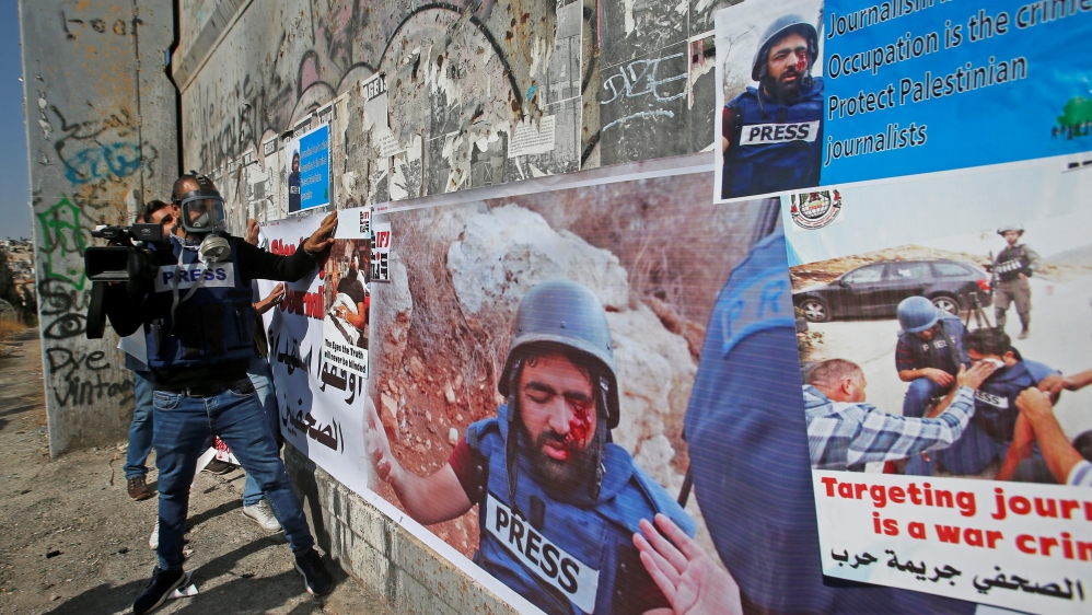 Palestinian journalists put on an Israeli gate posters showing their colleague Muath Amarna, who was shot in his eye, during a protest to show solidarity with him