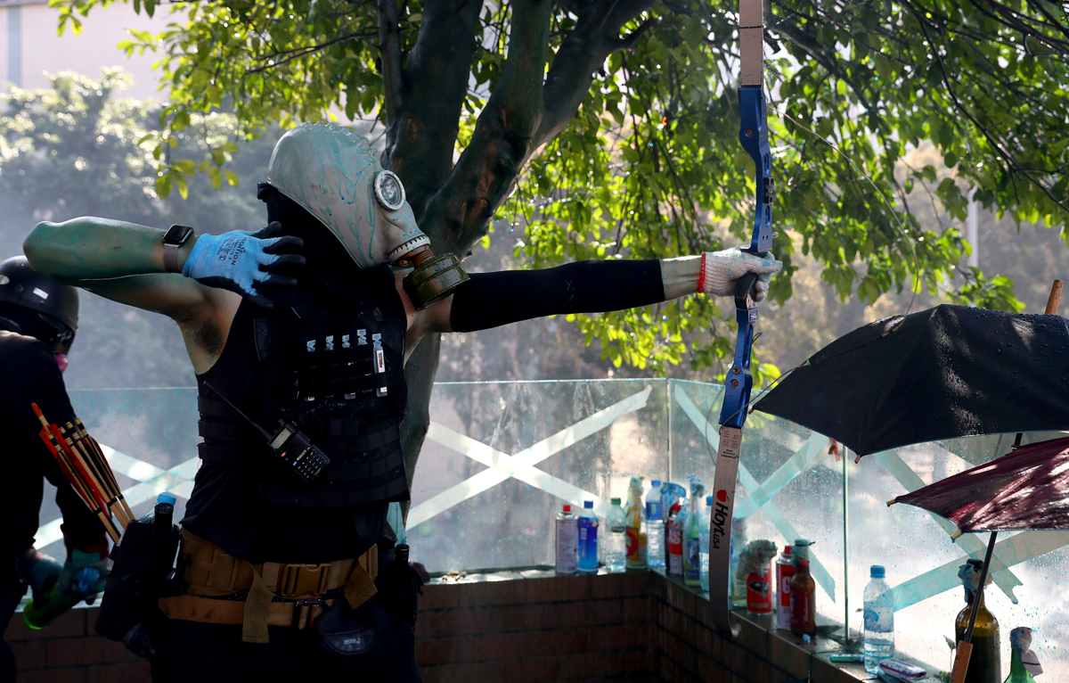 An anti-government protester uses a bow during clashes with police outside Polytechnic University. [Athit Perawongmetha/Reuters]