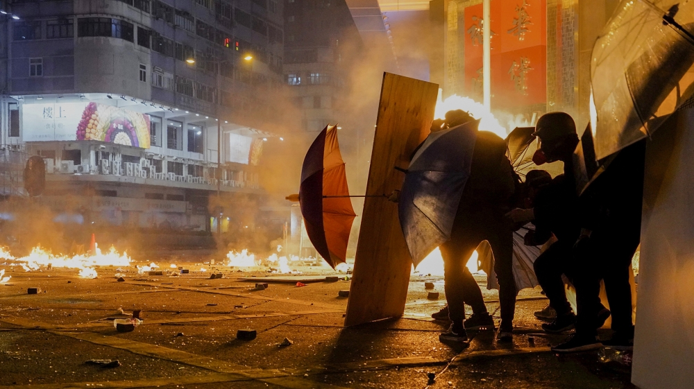Protestors react as police fire tear gas in the Kowloon area of Hong Kong, Monday, Nov. 18, 2019. As night fell in Hong Kong, police tightened a siege Monday at a university campus as hundreds of anti