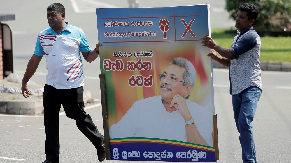 Supporters of Sri Lanka's President-elect Rajapaksa carry a poster of him in Colombo
