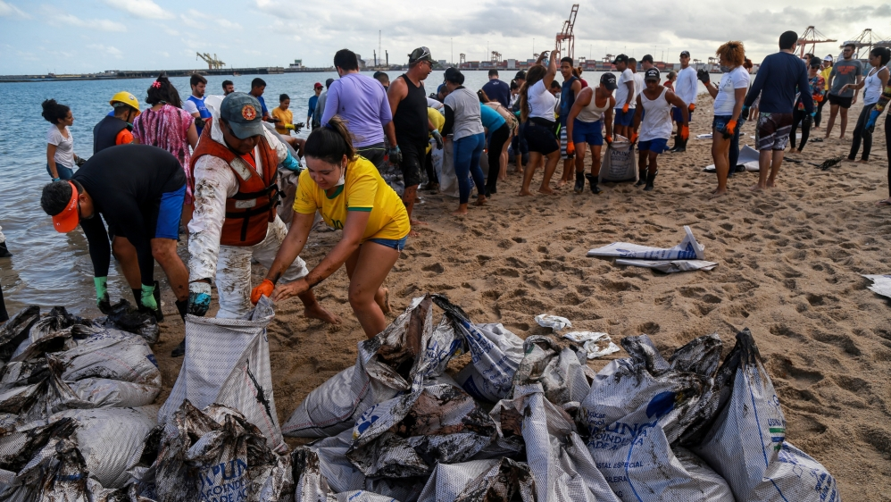 People work to remove an oil spill on Suape beach in Cabo de Santo Agostinho, Pernambuco state, Brazil October 20, 2019