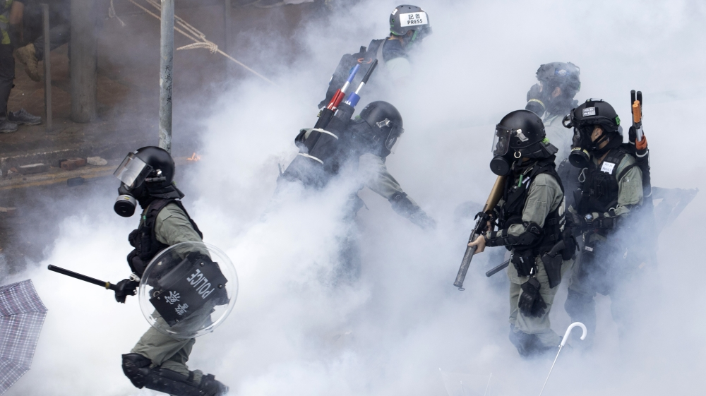 Police in riot gear move through a cloud of smoke at the Hong Kong Polytechnic University in Hong Kong, Monday, Nov. 18, 2019
