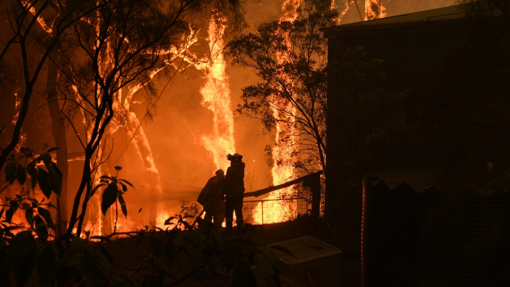 RFS volunteers and NSW Fire and Rescue officers protect a home on Wheelbarrow Ridge Road being impacted by the Gospers Mountain fire near Colo Heights south west of Sydney