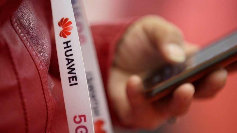 An attendee wears a badge strip with the logo of Huawei and a sign for 5G at the World 5G Exhibition in Beijing, China November 22, 2019