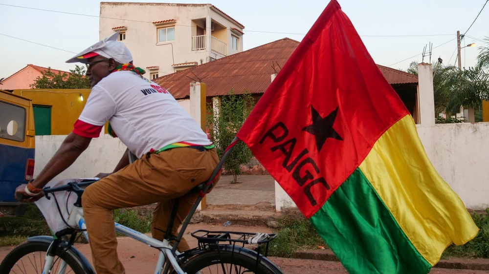 A supporter of presidential candidate Domingos Simoes Pereira rides a bicycle in Bissau