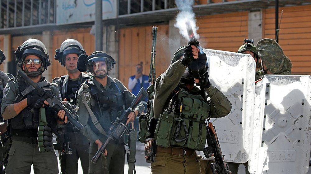 An Israeli soldier fires a weapon during a protest as Palestinians call for a day of rage over U.S. decision on Jewish settlements, in Hebron in the Israeli-occupied West Bank November 26, 2019. REUTE
