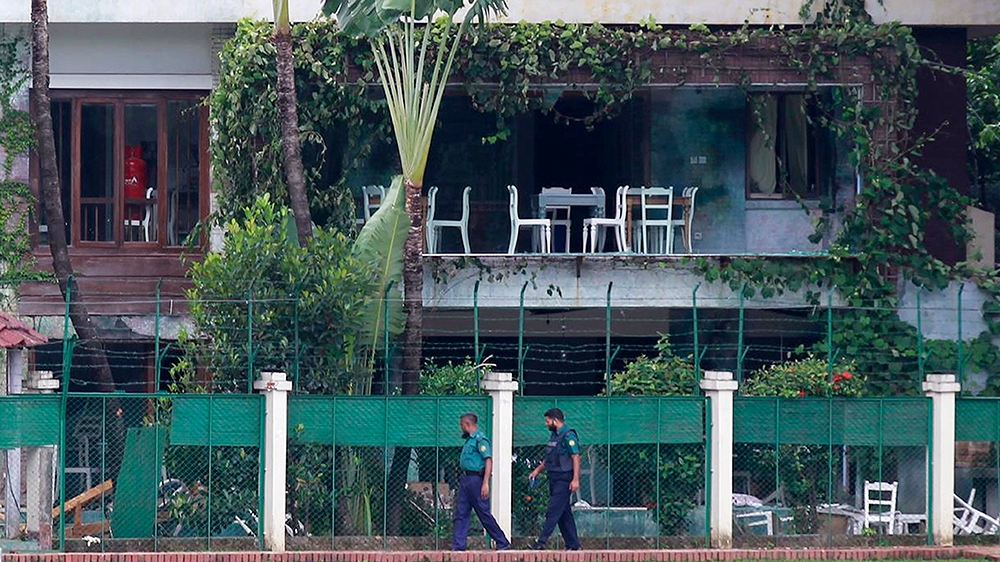 In this July 3, 2016 file photo, Bangladeshi policemen walk past the Holey Artisan Bakery in Dhaka's Gulshan area, Bangladesh, one day after heavily armed militants held dozens of people hostage at th
