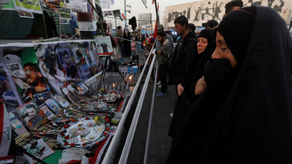 An Iraqi woman reacts as she looks at a makeshift memorial with personal belongings of those who were killed at an anti-government protests at Tahrir Square in Baghdad