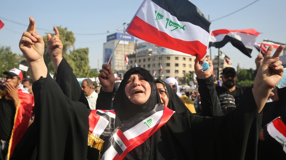 Iraqi women chant slogans and wave national flags as they take part in a protest in the capital Baghdad's Tahrir square during ongoing anti-government protests on November 4, 2019. Iraqi security forc