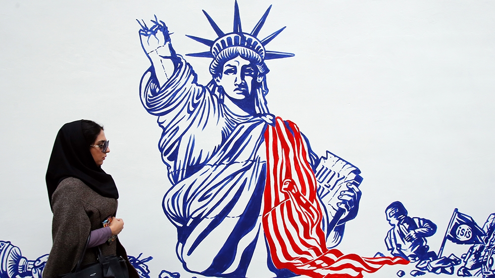 An Iranian woman walks past the new anti-US mural wall painting on the wall of the former US embassy during a ceremony in Tehran, Iran, 02 November 2019. Media reported that Iran unveiled new anti-US