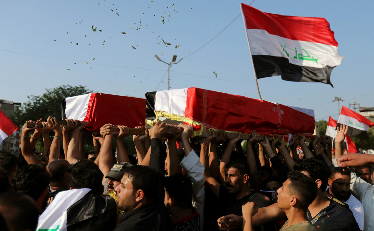 Iraqi mourners carry the coffin of a demonstrator who was killed during anti-government protests in the holy city of Karbala. [Abdullah Dhiaa al-Deen/Reuters]